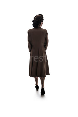 A silhouette of a 1940's mystery woman in a hat and coat, walking away – shot from eye-level.