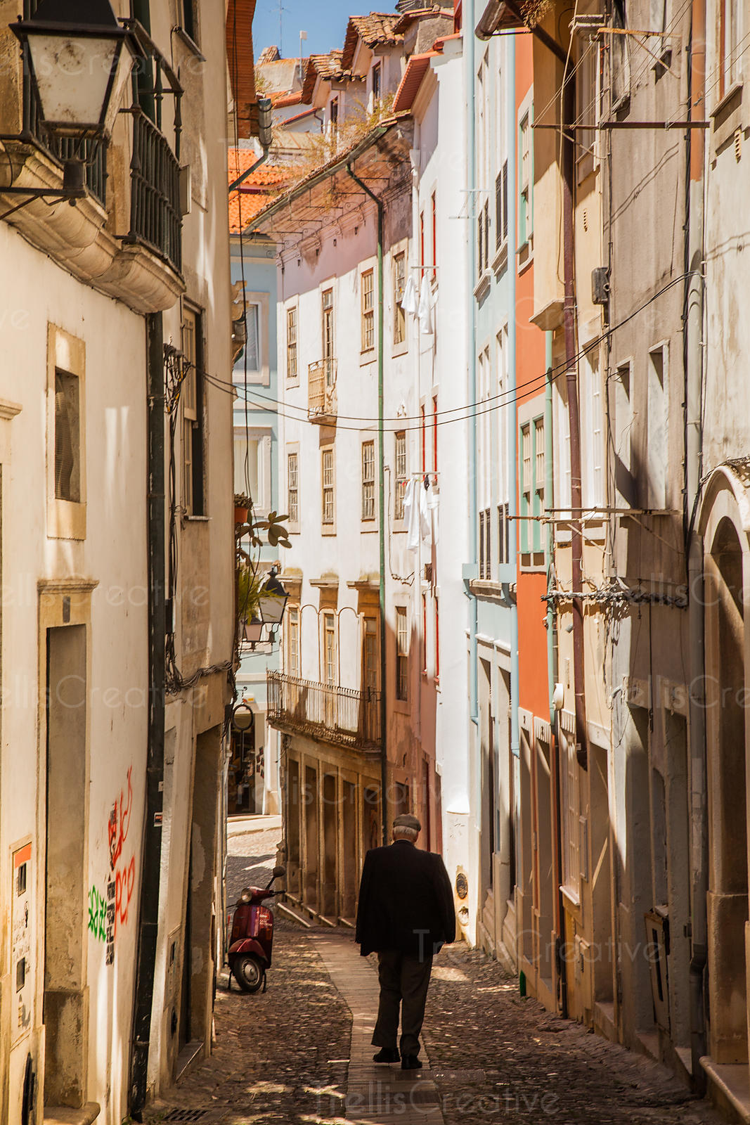 An old man walks down a colorful, narrow alley way in  Coimbra, Portugal