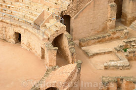 Looking down from the cavea to an exposed section showing the coridor behind the podium wall, This was used to coneal the animals and gladiators movements so their enterance could suprise the spectators. El Jem, Tunsia; Landscape