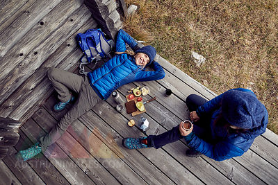 Overhead view of couple hikers having a break at mountain hut