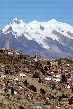 Suburbs spreading up hillside on outskirts of city, Mt Illimani in background, La Paz, Bolivia