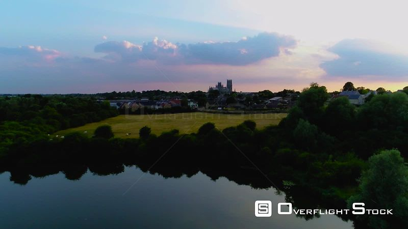 Aerial view of Ely Cathedral reflected in lake at sunset, filmed by drone in summer, United Kingdom