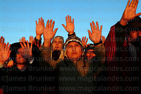 People hold up their hands to receive the sun's energy at sunrise during Aymara New Year celebrations, Tiwanaku, Bolivia