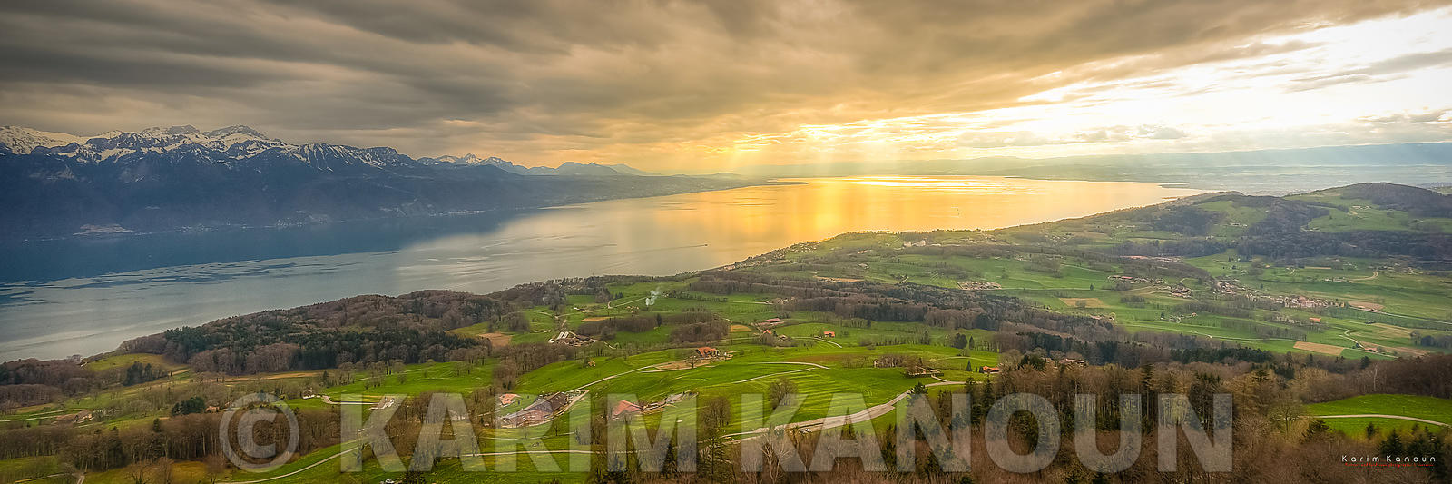 Dramtic sky with a golden hole in the clouds. View of the center part of Lake Geneva from Mont Pèlerin