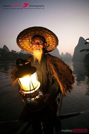 Chinese fisherman with lantern on boat, near Guilin, China