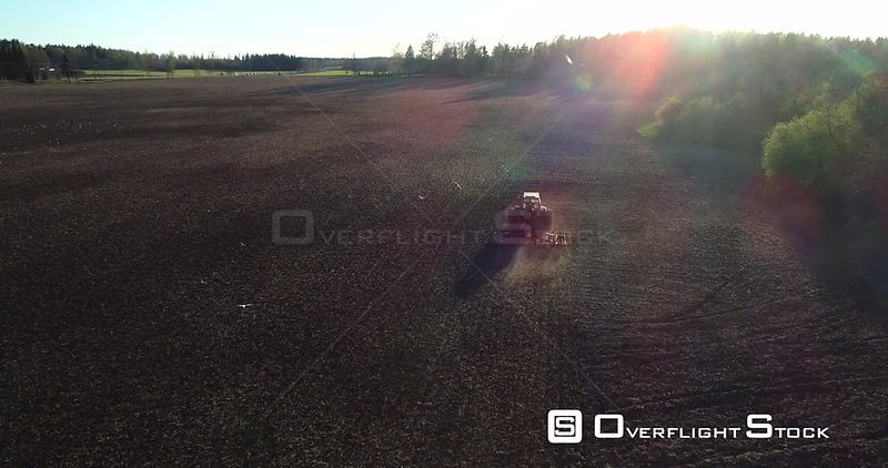 Spring Plowing, Aerial View of a Plow Machine Sowing and Birds Flying Around the Vechicle, Sunny Spring Evening Dawn, Uusimaa, South Finland