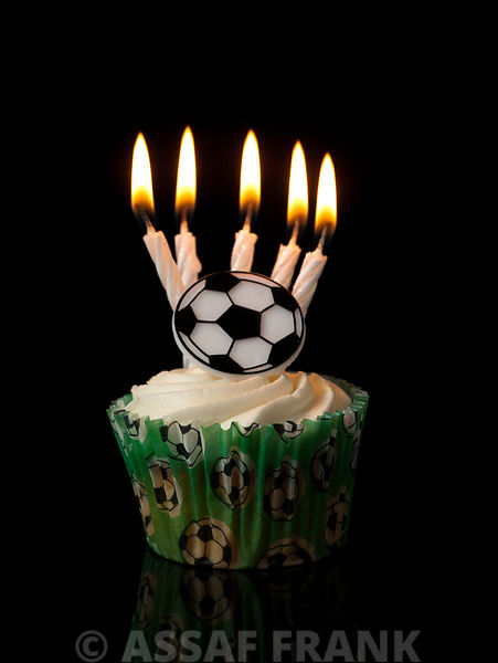 Cupcakes with football decoration and birthday candles