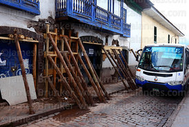 Wooden poles holding up collapsing wall of colonial building, Cusco, Peru