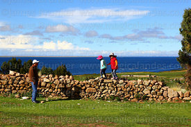 Dad watching daughters playing on stone wall, Lake Titicaca in background, Juli, Puno Region, Peru
