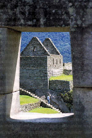 Inca house framed in window of Temple of the Three Windows, Machu Picchu, Peru