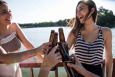 Friends relaxing together at sunlight toasting with beer bottles