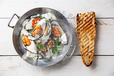 Shellfish Mussels Clams on pan with blue cheese sauce and bread