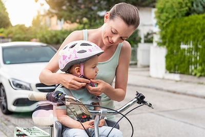 Mother and daughter, daughter wearing helmet sitting in children's seat