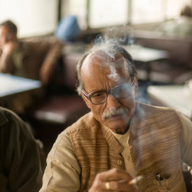 Mr Kumar smokes a cigarette in the Indian Coffee House, New Delhi