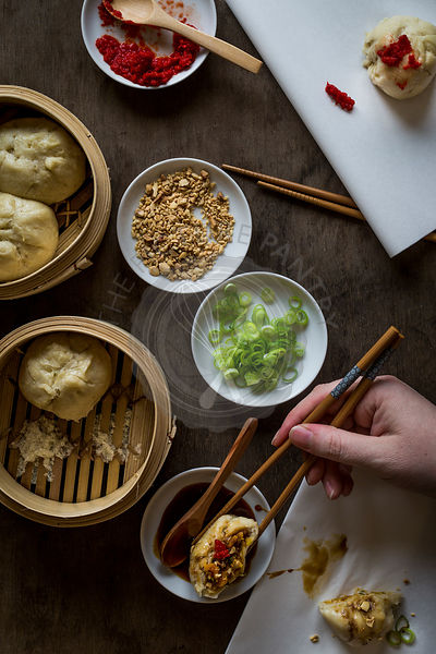 Woman's hand with chopsticks dipping stuffed dumpling in sauce on wooden tabletop with bamboo steamers. Top view