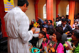 Priest blessing miniatures with holy water inside church after mass, Alasitas festival, Puno, Peru