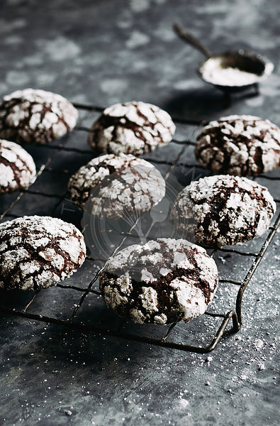 chocolate crinkle cookies in wooden box, dusted with icing sugar.