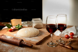 Table with pizza dough and wine glasses.