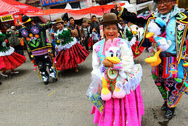 Cholita and chu'ta wearing Daisy and Donald Duck soft toys dancing during parades for the Entierro del Pepino, La Paz, Bolivia