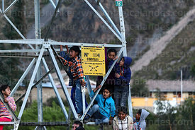 Children on an electric pylon watching a festival event next to danger of death sign, Ollantaytambo, Sacred Valley, Peru
