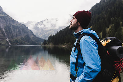 Austria, Tyrol, Alps, hiker standing at mountain lake