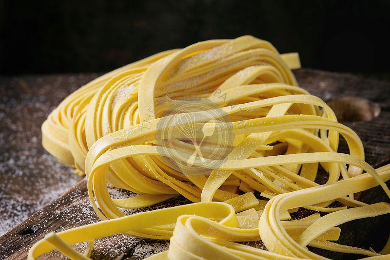 Raw uncooked homemade italian pasta tagliatelle