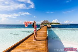Woman with sarong walking on jetty, Maldives
