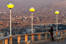 Hispanic woman looking at view over city from El Morro headland at sunset, Arica, Region XV, Chile