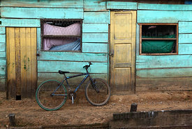 Bicycle propped against wall of typical wooden house , Rurrenabaque , Bolivia