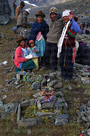 Family stand by small symbolic stone house and plot of land after challa (blessing ceremony), Qoyllur Riti festival, Peru