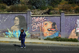 Woman crossing road in front of salchipapas mural, La Paz, Bolivia