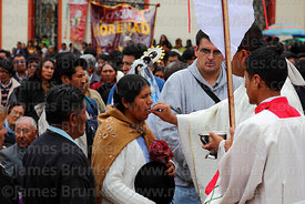 Aymara woman receiving holy communion after central mass, Virgen de la Candelaria festival, Puno, Peru