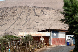 Geoglyphs at Cerro Sagrado, Chilean flag on side of house, Azapa Valley , Region XV , Chile