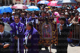 Devotees of Señor de los Milagros holding banner during central mass for the Virgen de la Candelaria festival, Puno, Peru