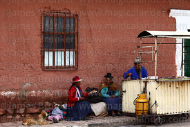 Indigenous women sitting next to street food stall outside colonial house, Lampa, Peru