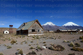 Abandoned timber house, Payachatas volcanos in background, Caquena, Region XV, Chile