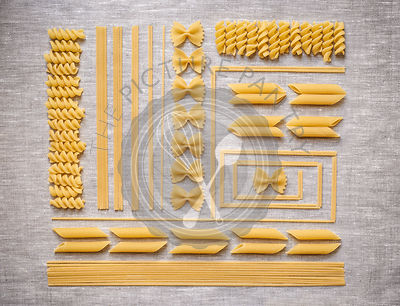 Artistic layout of dry pasta in multiple shapes and sizes.