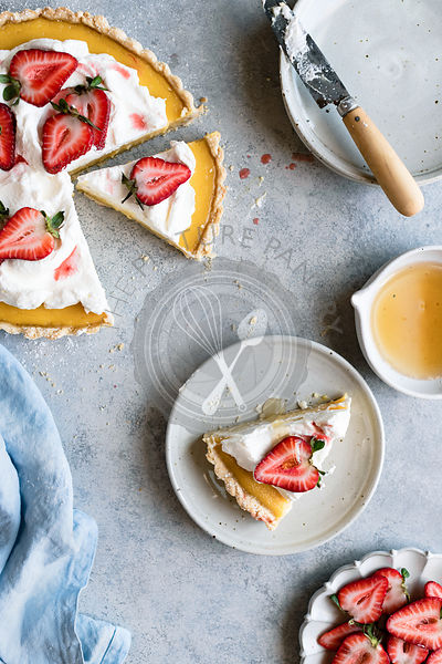 Lemon Tart served with cream, strawberries, and honey