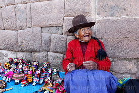 Old Quechua woman from Chinchero selling textile dolls in front of Inca walls, Cusco, Peru