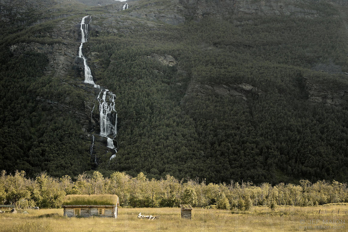 Log house with grass-covered roof by mountain and waterfall