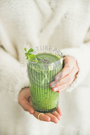 Matcha green smoothie with chia seeds in female hands
