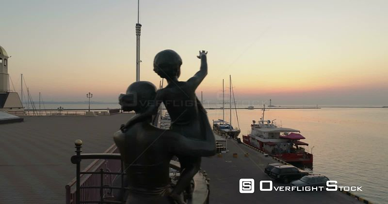 Drone flies at low level past the statue of the seafarers at the Odessa cruise terminal in Ukraine. The sun is rising behind. Ukraine