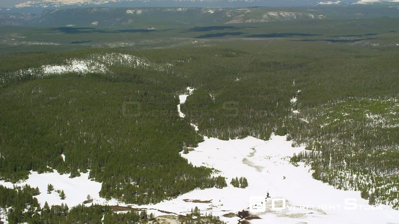 An open meadow sits in dense lodgepole forests in Yellowstone National Park, with the Henry's Lake and Madison mountain Ranges towering in the background