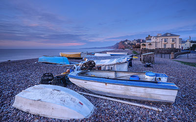 Serene dawn scene of fishing boats on the pebbled beach at Budliegh Salterton, Devon, UK