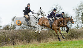 Willa Newton, Callie Coles jumping a hedge by Puss's Bushes - The Cottesmore at The Fox and Hounds