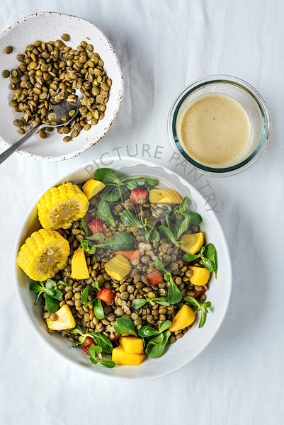 Lentil salad with herbs, tomatoes and peaches in a white bowl is photographed from top view. It is accompanied by cooked lentils in a bowl and tahini dressing.