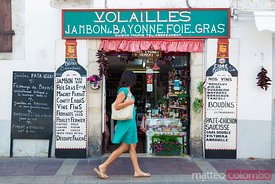 Woman walking in front of regional food shop, Basque country, France