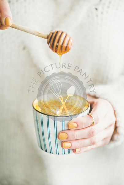 Turmeric latte, golden milk with honey in woman's hands, close-up