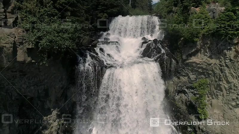 Drone flight backwards floating slowly with the flow of Alexander Falls by Whistler in British Columbia Canada