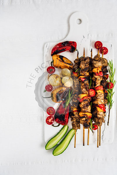 Lamb shish kebab served with grilled peppers, shallots, fresh cherry tomatoes and cucumber on a white marble board photographed from top view.